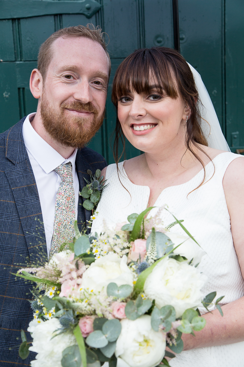 Couple smiling at each other at Elsecar Heritage Centre on their wedding day