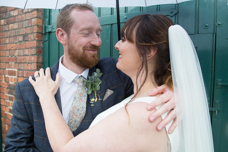 Couple smiling with a white umbrella at Elsecar Heritage Centre on their wedding day