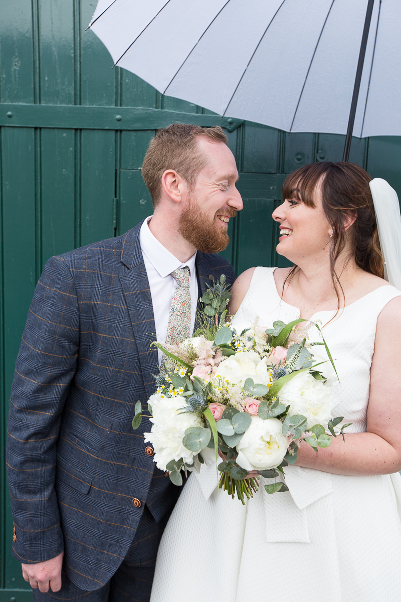 Couple laughing together with a white umbrella at Elsecar Heritage Centre on their wedding day