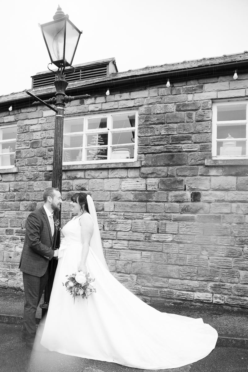 Couple next to a lamp post on a rainy wedding day at Elsecar Heritage Centre on their wedding day