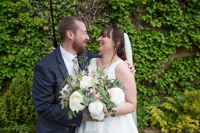 Couple laughing at Elsecar Heritage Centre on their wedding day