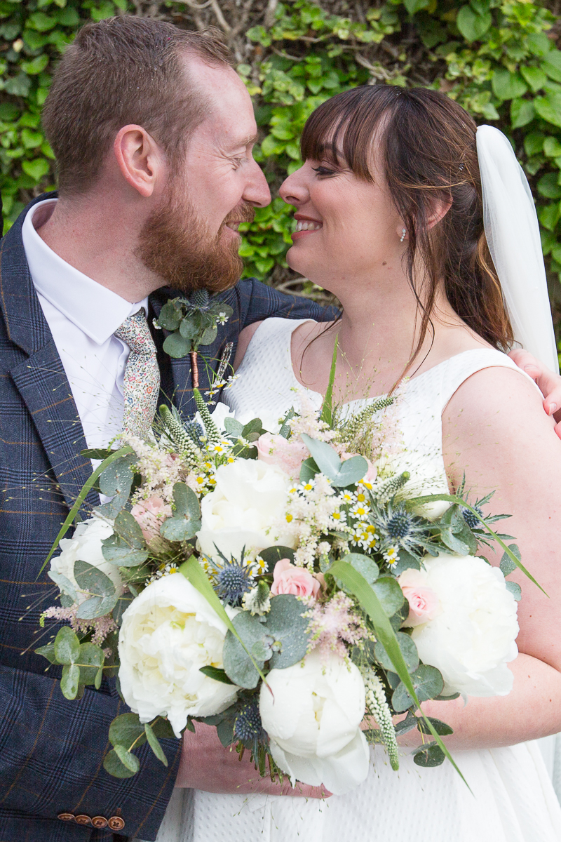 Newlyweds smiling at each other at Elsecar Heritage Centre on their wedding day
