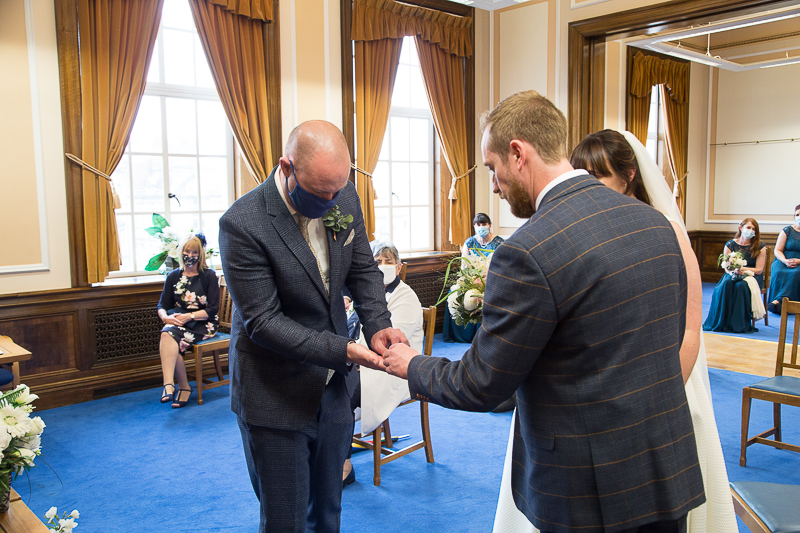 Best man giving the wedding rings to the groom at Barnsley Town Hall wedding Photographer South Yorkshire