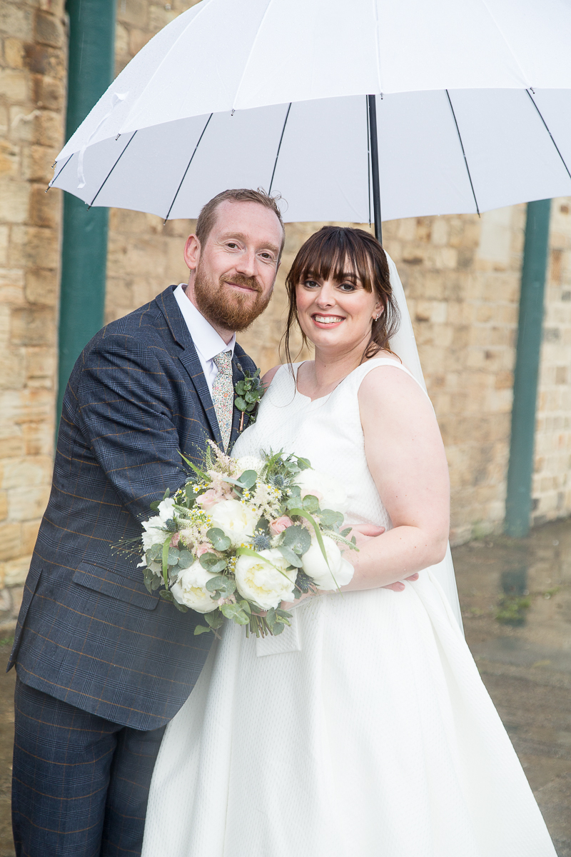 Couple smiling with an umbrella on a rainy wedding day