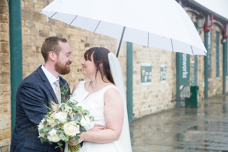 Couple smiling in the rain at Elsecar Heritage Centre on their wedding day