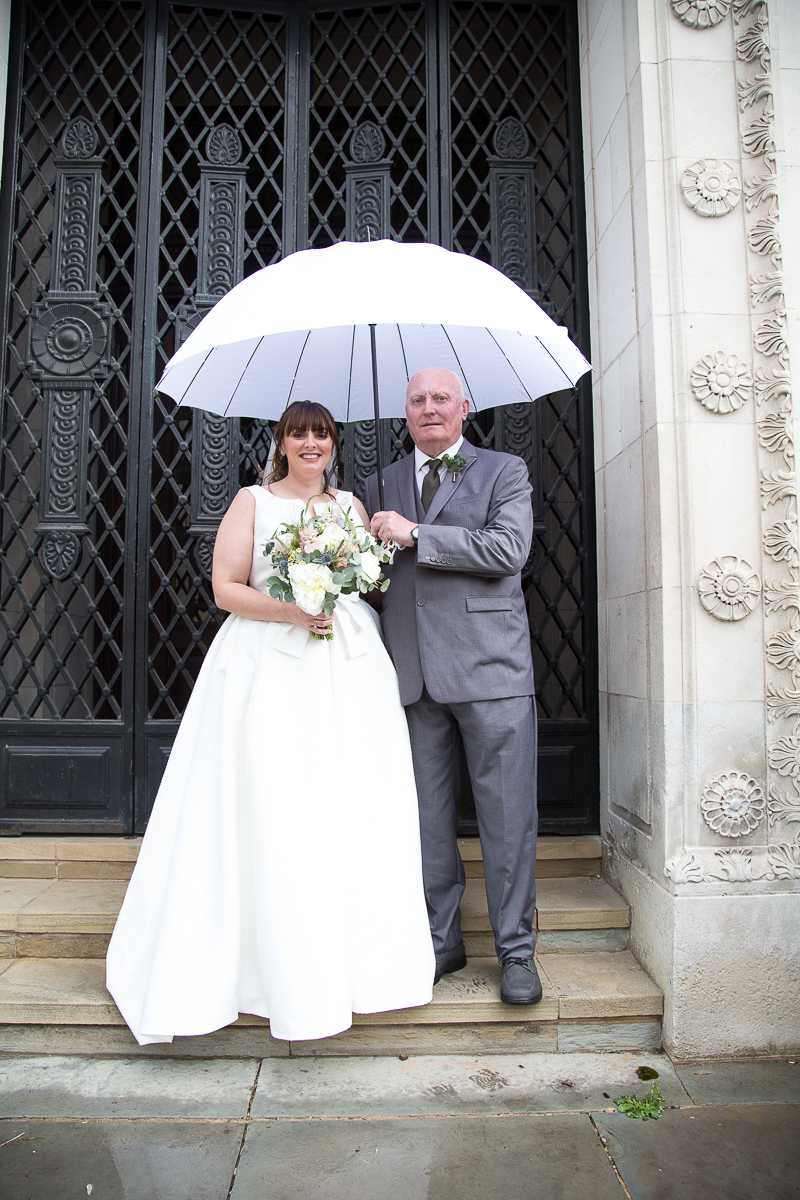 Bride outside Barnsley Town Hall with her Dad Rainy Wedding Day