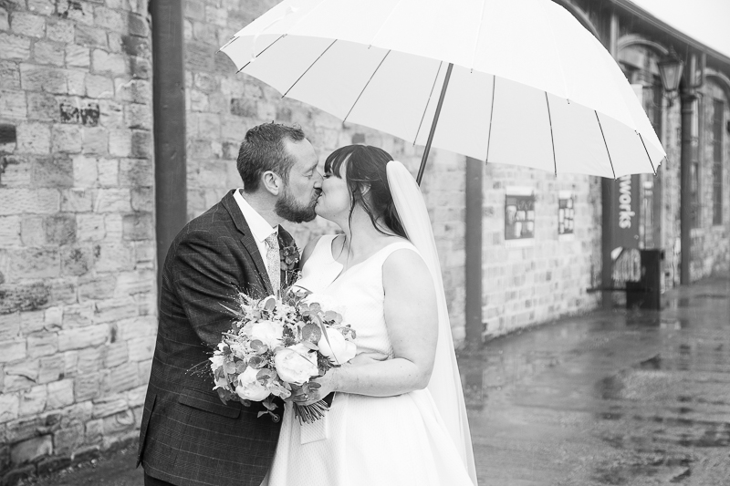 Couple kissing next to the ironworks at Elsecar Heritage Centre on their wedding day