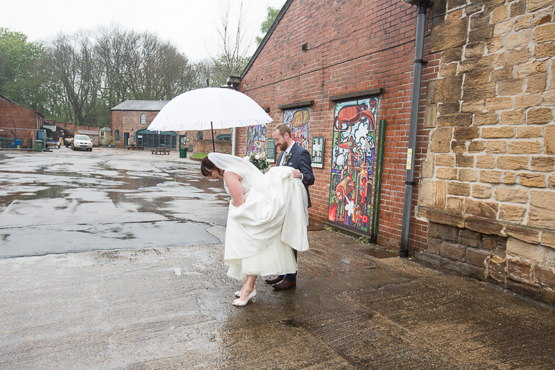 Bride stepping in a puddle at Elsecar Heritage Centre on their wedding day