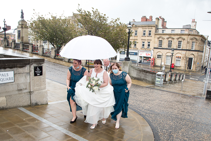 Bridesmaids walking to the Barnsley Town Hall wedding ceremony with masks in the rain