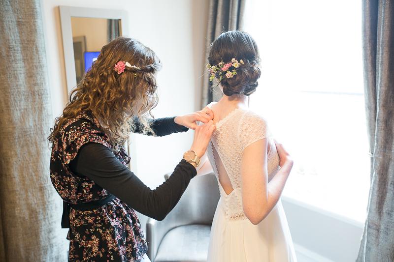 Bridesmiad fastening the wedding dress at Cubley Hall, Penistone
