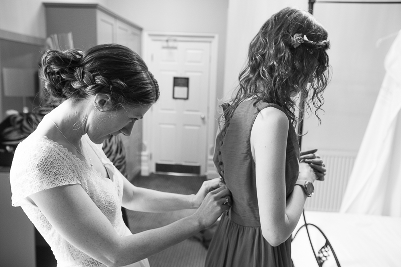 Bride fastening bridesmaid dress on the morning of the wedding
