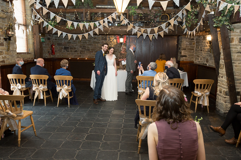 Couple smiling for guests at the altar in Cubley Hall wedding ceremony