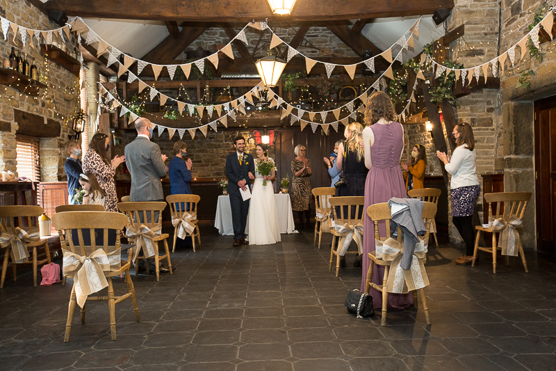 Guest clapping as couple walk back up the aisle at Cubley Hall Wedding
