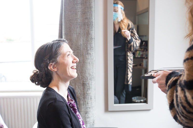 Bride and Makeup artist laughing on the morning of her wedding