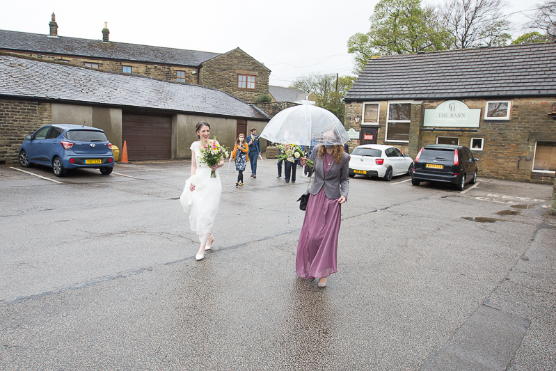 Guests walking across the car park in the rain at covid wedding in Cubley Hall Hotel