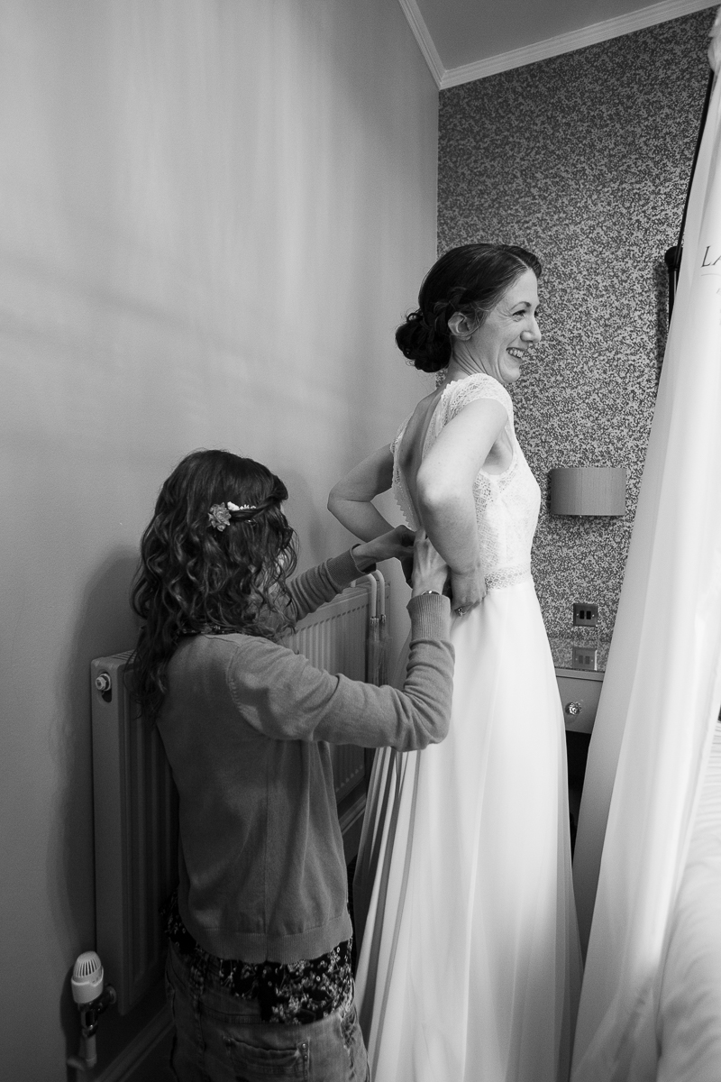 Bridesmaid fastening the wedding dress at Cubley Hall Sheffield