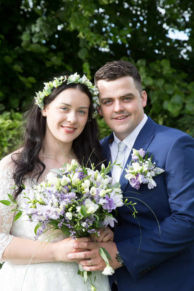 Bride with flower headband and groom in blue suit on their wedding day at Waterton Park Hotel