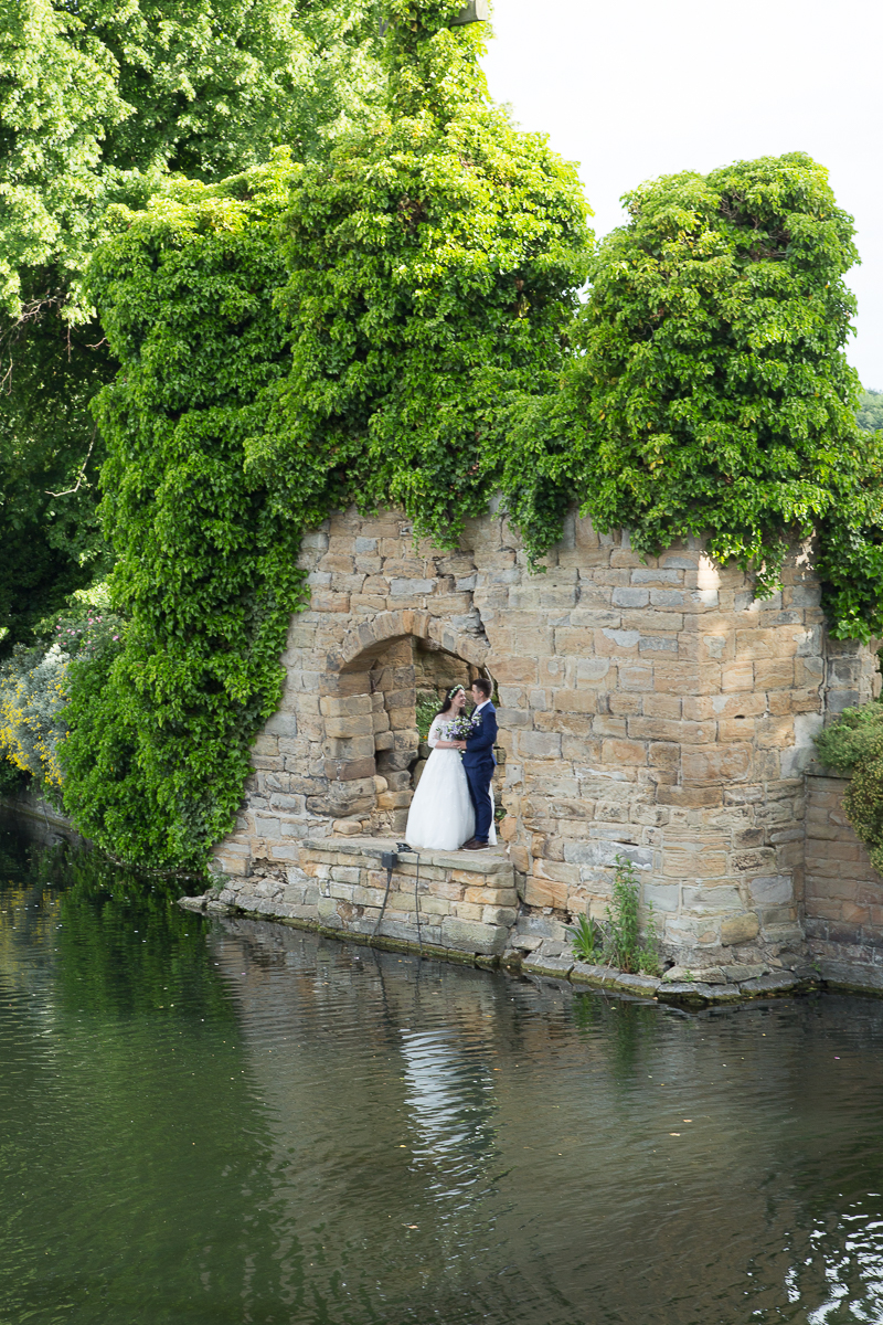 Bride and groom across the water at Waterton Park Hotel