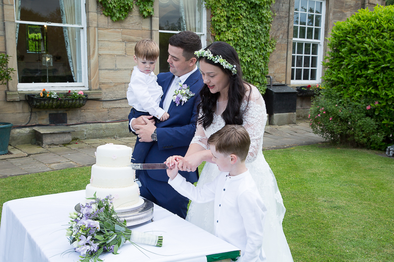 Bride and groom cutting cake with the page boys at Waterton Park Hotel wedding