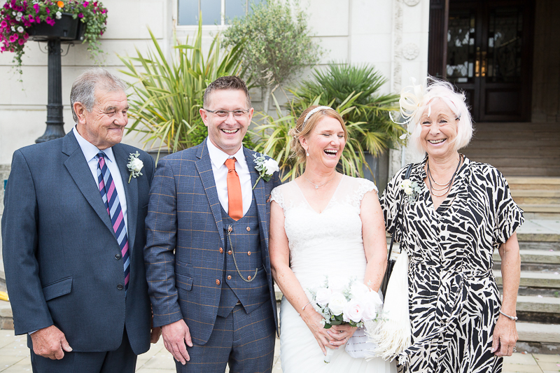 Guests laughing with bride and groom outside barnsley town hall