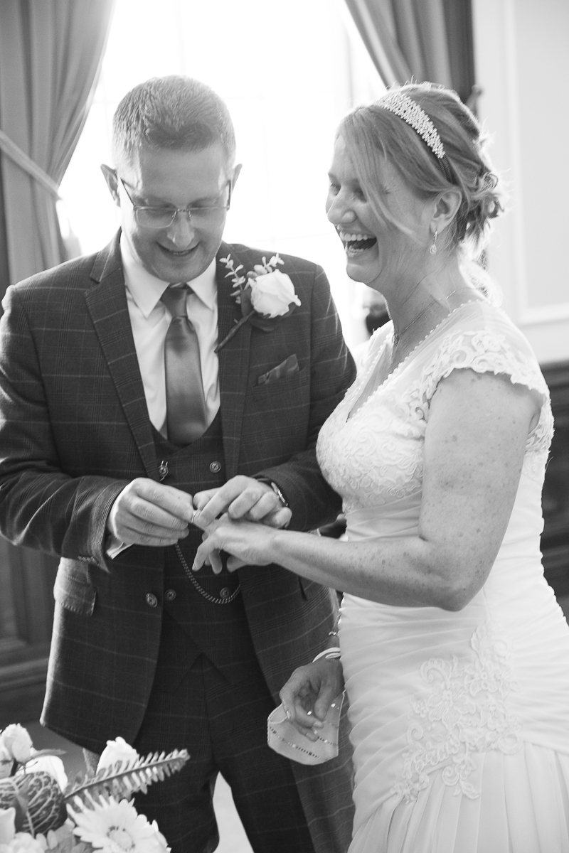 Couple laugh during ring exchange at their wedding ceremony at Barnsley Town Hall