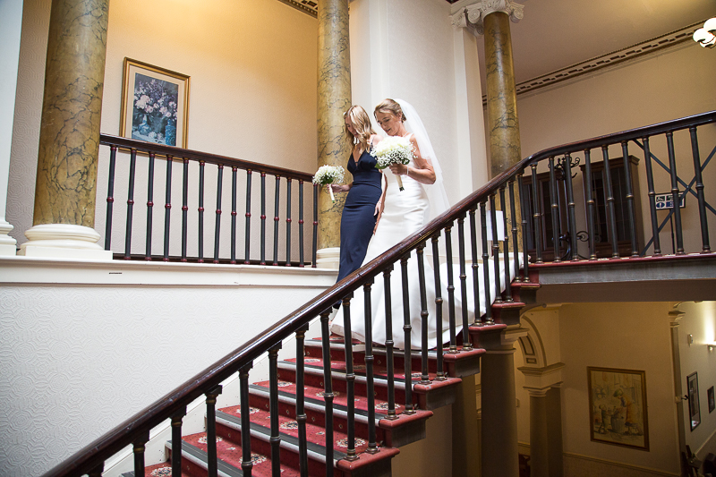 Bride and her maid of honor walking down the stars at Wortley Hall Sheffield Wedding